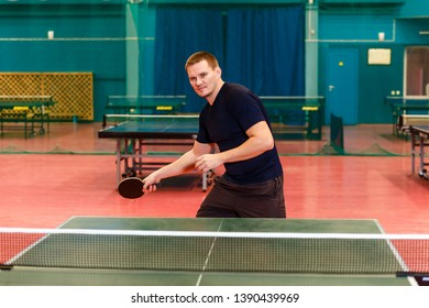 young thirty-year-old man playing ping pong indoors