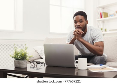 Young thoughtful african-american man at home chatting online on laptop with friend. Casual guy sitting on beige couch in light livingroom, copy space