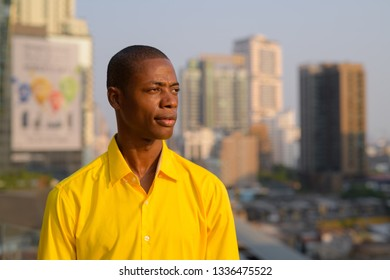Young thoughtful bald African businessman against view of the city