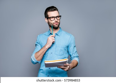 Young thoughtful bearded man in glasses thinking about test.