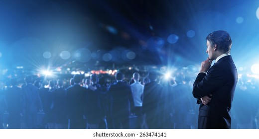 Young thoughtful businessman and crowd of business people