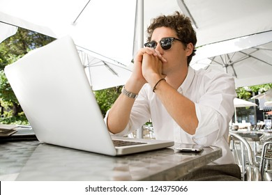 Young thoughtful businessman sitting with his laptop computer at a coffee shop terrace, outdoors.