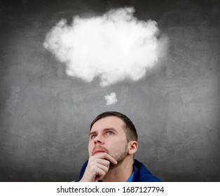 Young thoughtful businessman sitting on the floor with white cloud over head. Over gray wall background.