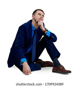 Young thoughtful businessman sitting on the floor. Isolated on white background.
