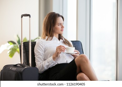 Young thoughtful businesswoman drinking coffee with baggage sitting in airport or hotel room, beautiful woman waiting for flight or relaxing after arrival travelling on business with  travel bag