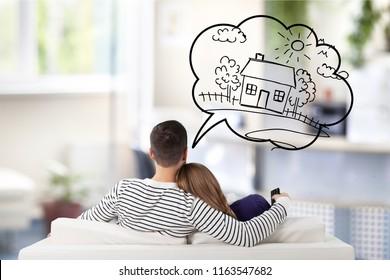 Young Thoughtful Couple Sitting On Sofa Thinking