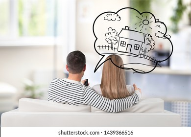 Young Thoughtful Couple Sitting On Sofa Thinking