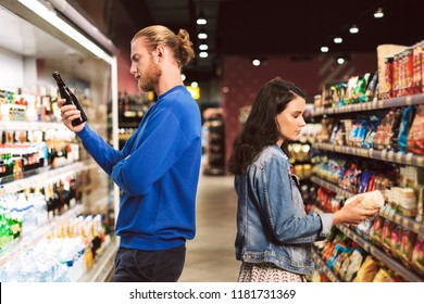 Young thoughtful couple standing back to back choosing products spending time in modern supermarket