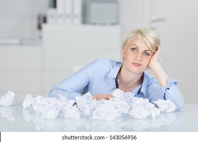 Young thoughtful female executive sitting with crumpled paper balls at desk looking in camera