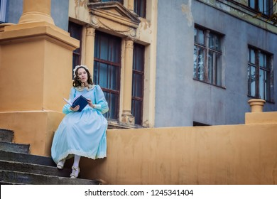 Young, thoughtful girl in a blue vintage dress reads a love story on the stairs of the castle