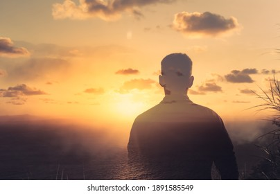 Young thoughtful man in a beautiful sunrise setting looking out from a mountain top. Nature getaway, and finding peace in nature concept. Double exposure