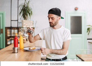 Young thoughtful man in black cap sitting at the bar counter and holding salt while eating burger in cafe