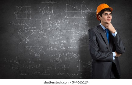 Young thoughtful man engineer in helmet and sketches on wall