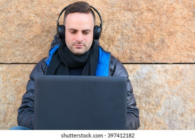 Young thoughtful man in headphones sitting on street while using laptop. Granite wall on background