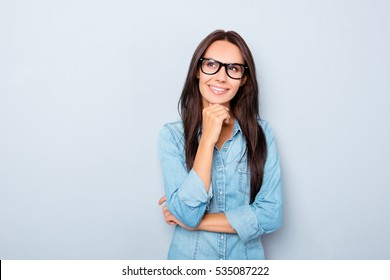 Young thoughtful secretary in glasses dreaming on gray background