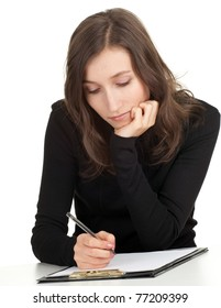 young thoughtful woman with brown hair writing on clipboard