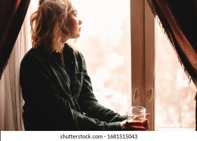 Young thoughtful woman drinking tea and looking through window while sitting on windowsill at home