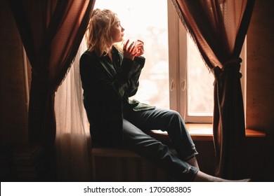 Joven mujer considerada tomando té y mirando por la ventana mientras se sienta en casa en la ventana