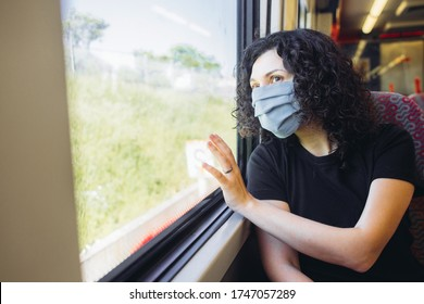 Young thoughtful woman in a medical mask in a train, touching a window. Concept of travelling and using public transport during quarantine