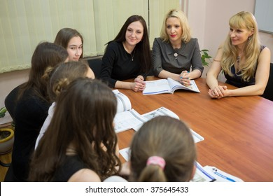 Young three teachers (focus on woman in gray dress) are sitting at table with books and talking to five students in classroom.