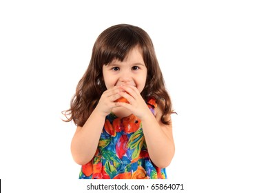 Young three year old girl about to bite a piece of fruit on a white background