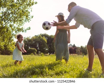 A young three-member family spends the afternoon in the park and plays with a soccer ball. Family runs out together. Family leisure activities.