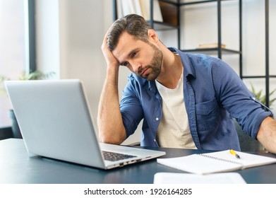 Young tired bearded office worker freelancer in casual clothes sitting at the desk at his workplace, supporting head with hand and looking at the laptop screen, feeling overworked and sleepy