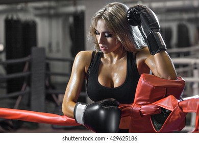 Young tired boxer woman standing on ring and resting. Sweat wet skin.