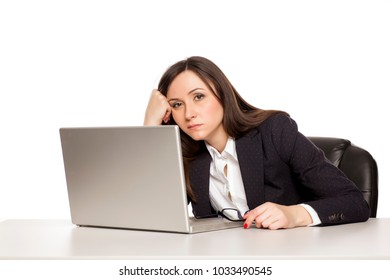 young tired business woman sitting at a desk with a laptop