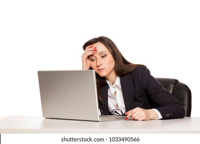 young tired business woman working at a desk with a laptop