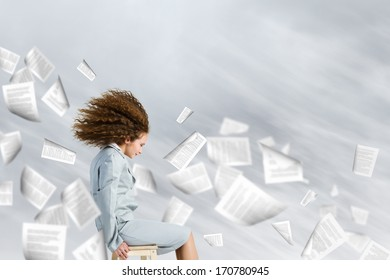 Young tired businesswoman with waving hair among flying documents