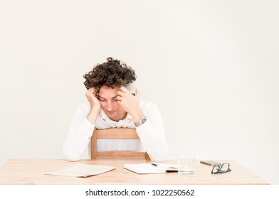 Young tired Caucasian freelancer man sitting in his home office at the table in front of empty clear wall.