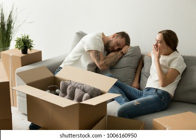 Young tired couple feeling fatigue on long hard moving out day, exhausted restless man having break in new home while sleepy woman yawning on sofa after packing staff in boxes preparing to relocate