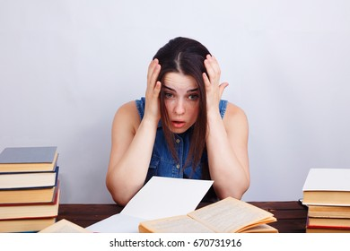 Young tired desperate student woman sitting at the table with text books. Stress, overwork concept