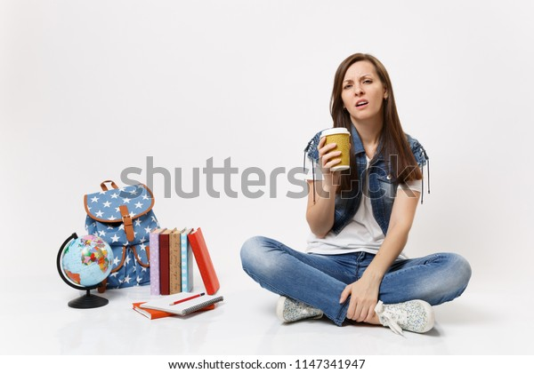 Young tired exhausted woman student holding paper cup with coffee or tea sitting near globe, backpack, school books isolated on white background. Education in high school university college concept