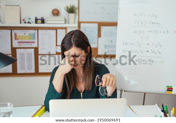 Young tired female professor having headache. Teacher holding online class for e-learning students at home during COVID-19 pandemic period. Stressed woman take off glasses feel pain rub closed eyes