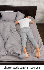 Young tired male wearing pajama sleeping without blanket in stylish bed in a loft style bedroom