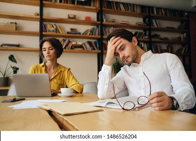 Young tired man sitting at the table with notepad and eyeglasses thoughtfully holding hand near head at work in office with colleague on background
