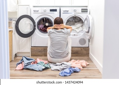 Young Tired sad Woman sitting on the floor in laundry room, back view
