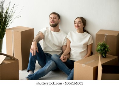 Young tired satisfied couple relaxing on floor with boxes, happy homeowners holding hands dreaming of future changes in new home after relocation, man and woman feeling pleasant fatigue on moving day