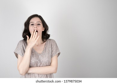 Young tired sleepy disinterested woman yawning isolated on white background, funny lazy bored girl feeling deprived drowsy somnolent on light blank studio wall, lack of sleep gape and boredom concept.