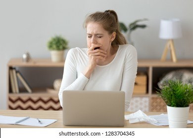 Young tired sleepy woman yawning working or studying with laptop, funny lazy bored student feeling deprived drowsy after sleepless night of dull exam preparation, lack of sleep and boredom concept