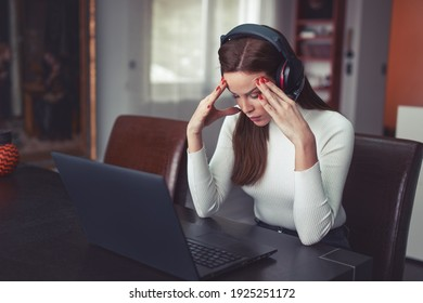 Young tired smart Caucasian woman in headset has headache at laptop, indoors