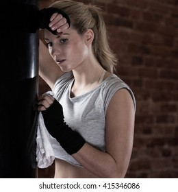 Young tired sweat girl leaning on punching bag after training