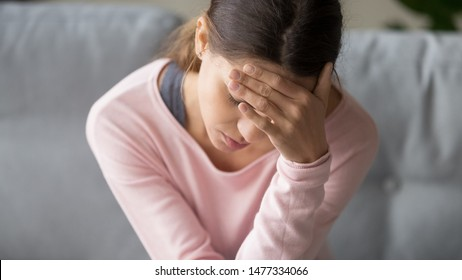Young tired unhealthy mixed race woman sitting on couch in living room at home with closed eyes, holding head with hand, suffering from strong sudden headache or migraine, throbbing pain.