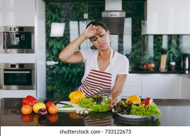 The young tired woman in apron in the kitchen. Healthy food - Vegetable salad. Dieting concept. Healthy lifestyle. Cooking at home. Prepare food