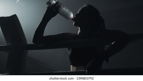 Young tired woman drinking from the water bottle after training in the dark boxing ring with smoke. Silhouette. Boxing concept