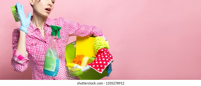Young tired woman holding cleaning tools and products in bucket saying no to cleaning, isolated on pink