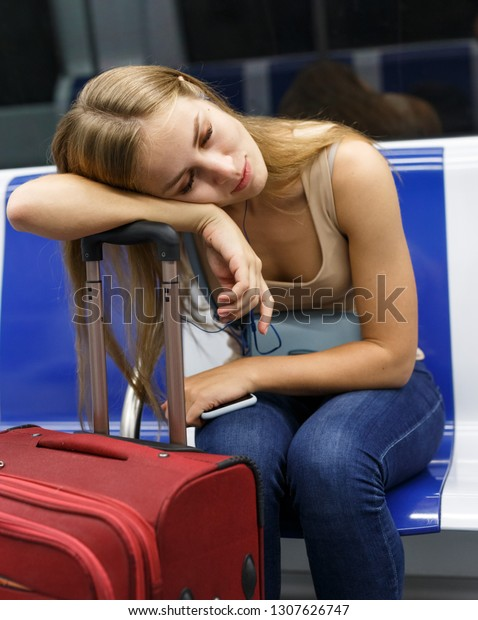 Young tired woman with red suitcase sitting in subway train