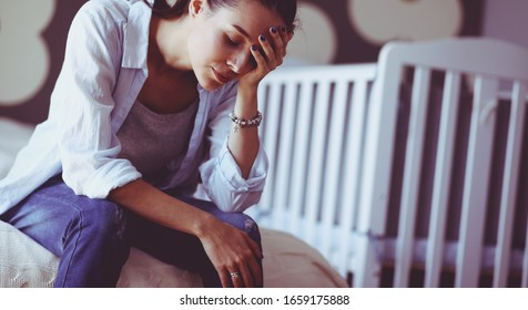 Young tired woman sitting on the bed near childrens cot